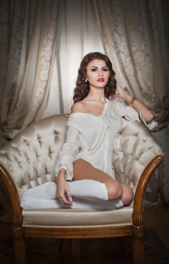 Beautiful young woman in white sitting on sofa posing provocatively in boudoir scenery. Attractive brunette girl with long hair and white long stockings laying down on vintage chair in bedroom