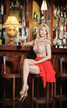Attractive blonde woman with long hair in elegant nude and red dress sitting on bar stool. Gorgeous blonde model showing her long legs with high heels posing provocatively in vintage bar