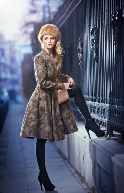 Attractive elegant blonde young woman wearing an outfit with Russian influence in urban fashion shot. Beautiful fashionable young girl with long legs and fur cap posing on street