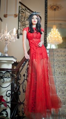 The beautiful girl in a long red dress posing in a vintage scene. Young beautiful woman wearing a red dress in an old hotel. Sensual elegant young woman in red long dress indoor shot.