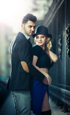 Couple in love in railway station. Beautiful well-dressed couple standing on railway platform. Handsome brunette young man holding a fashionable blonde with hat next to a train
