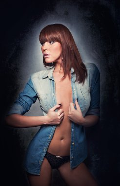 Attractive red hair model with black panties and denim shirt standing on gray background. Fashion portrait of a sensual woman - studio shot. Beautiful redhead female in denim posing provocatively.