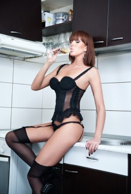 Attractive sexy red hair female with black lingerie and stockings drinking wine in a modern kitchen. Portrait of sensual redhead with black corset and long legs in modern scenery - indoor shot