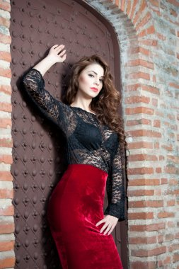 Charming young brunette woman in black lace blouse, red skirt and high heels near the brick wall. Sexy gorgeous young woman near old wall. Full length portrait of a sensual woman with long curly hair
