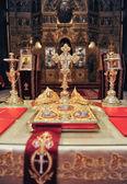 Kreuze, Ringe und Kronen aus Gold auf dem Tisch in der Kirche. Hochzeitsfeier