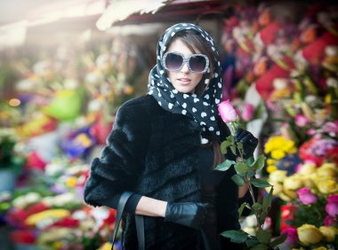Beautiful brunette woman with gloves choosing flowers at the florist shop. Fashionable female with sunglasses and head scarf at flower shop. Pretty brunette in black choosing flowers - urban shot