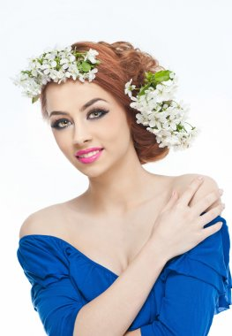 Portrait of beautiful girl in studio with spring flowers in her hair. Sexy young woman in blue with bright white flowers. Creative hairstyle and makeup, fashion photo studio shot