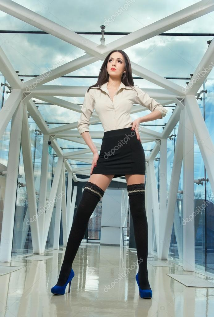 Sensual elegant woman in office outfit posing in a modern scenery. Beautiful and sexy brunette young woman wearing an elegant black and white outfit indoor. Fashionable model in steel and glass space.