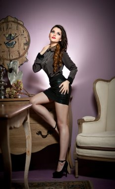 Young beautiful woman in black in a vintage room.Beautiful young woman with long legs in a classic interior. Seductive woman wearing short black skirt and high heels in luxury manor, vintage style