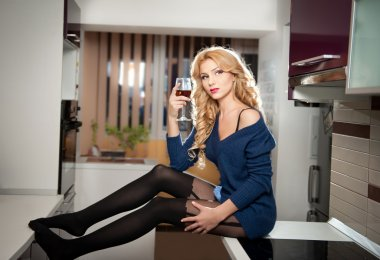 Attractive sexy blonde female with bright blue blouse and black stockings posing smiling holding a glass with red wine. Portrait of sensual fair hair woman with long legs in modern kitchen
