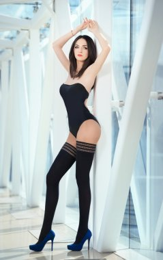 Sensual elegant woman wearing a black body posing in a modern scenery. Beautiful and sexy brunette young woman with high heels and black stockings indoor. Fashionable model in steel and glass space.