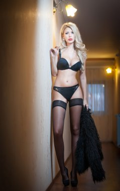 Attractive sexy blonde in black lingerie posing provocatively indoor. Portrait of sensual woman wearing black lingerie in classic boudoir scene. Woman with long hair and black stockings against a wall