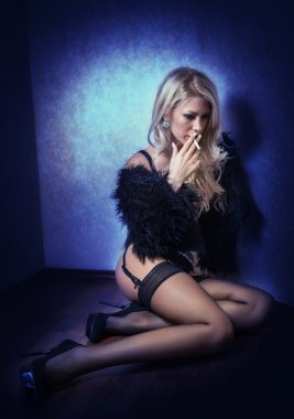 Attractive sexy blonde in black lingerie posing provocatively indoor. Portrait of sensual woman wearing black lingerie in classic boudoir scene. Fair hair woman sitting on the floor and smoking