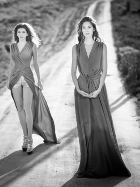Two young fashionable women waking on country side road, black and white photo. Attractive women on the field - outdoor shoot. Glamorous females with long dresses in nature