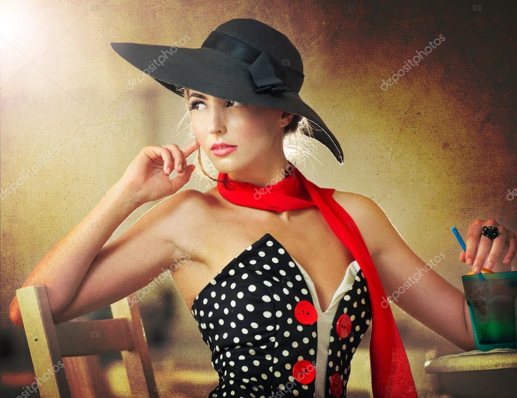 Fashionable attractive lady with black hat and red scarf sitting on chair in restaurant, indoor shot. Young woman posing in elegant scenery. Art photo of elegant sensual woman, vintage style