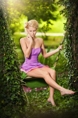 Beautiful young woman in pink short dress dreaming in a leaves decorated swing between two trees. Gorgeous fair hair girl posing in garden, outdoor shot. Attractive blonde swinging on leafy swing