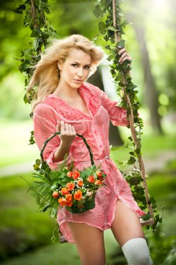 Beautiful young woman in pink short dress holding a basket with flowers in a leaves decorated swing. Gorgeous fair hair girl posing in garden, outdoor shot. Attractive blonde swinging on leafy swing