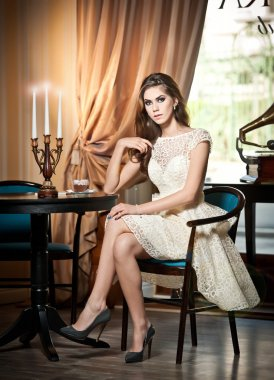 Young beautiful brunette woman in elegant lace dress sitting near a table with candlestick. Long hair attractive girl in luxurious classic interior. Seductive female in vintage scenery, indoor