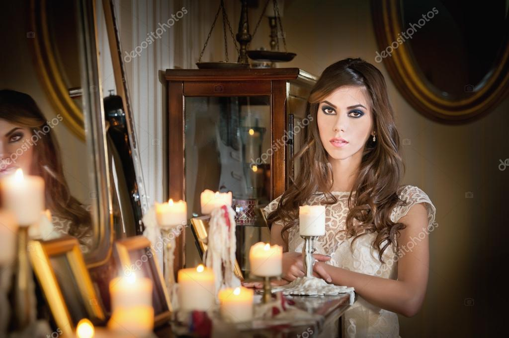 Beautiful sexy woman in white lace dress in vintage scenery with candles. Portrait of long hair brunette girl posing in luxury indoor. Attractive young fashionable female with creative makeup.