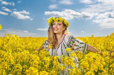 Young girl wearing Romanian traditional blouse posing in canola field with cloudy sky in background, outdoor shot. Portrait of beautiful blonde with flowers wreath smiling in rapeseed field