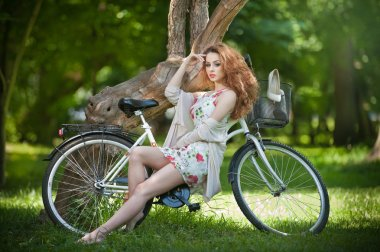 Beautiful girl wearing a nice short dress having fun in park with bicycle. Pretty red hair woman with romantic look posing sitting on her bike in a sunny day. Gorgeous curly redhead relaxing outdoor.
