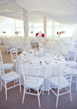 Wedding tables setting in white color. Tables set for an event party or wedding reception. Elegant table setting in restaurant. White arrangement for wedding.