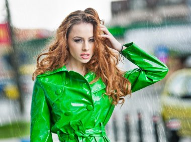 Beautiful woman in bright green coat posing in the rain. Dramatic redhead staying in the rain drops, urban shot. Attractive red hair girl on the street in a rainy day. Emotional pretty young female.