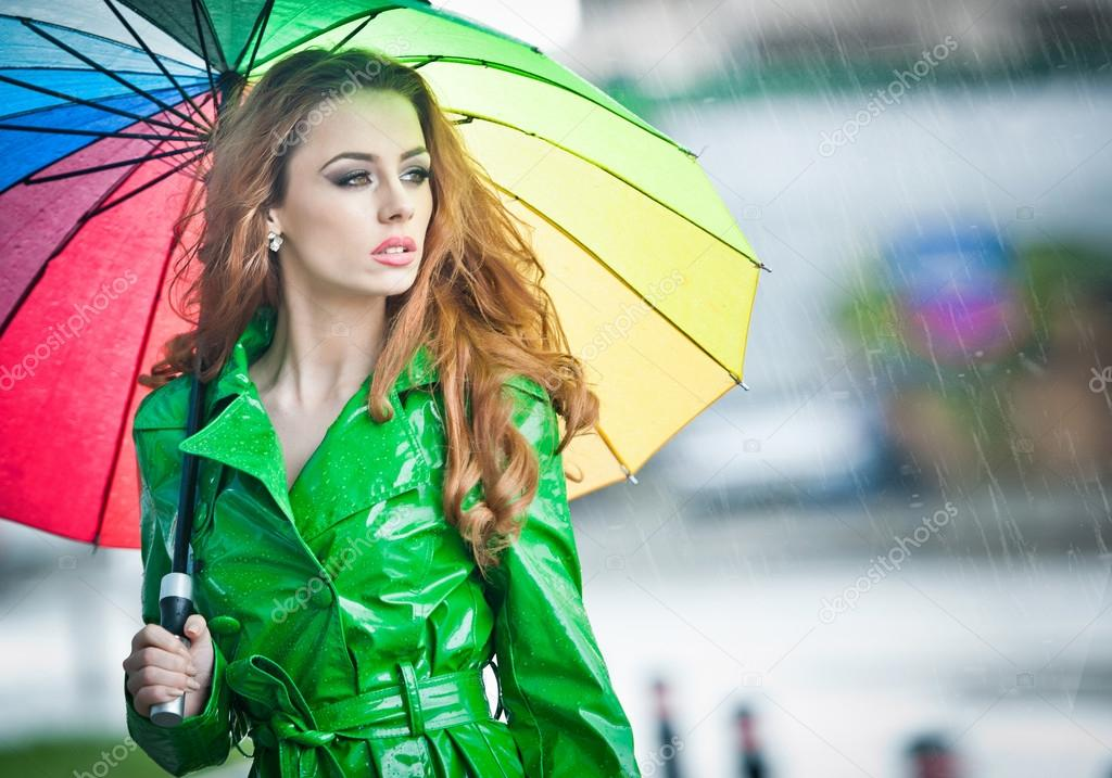 Beautiful woman in bright green coat posing in the rain holding a multicolored umbrella. Dramatic redhead staying under umbrella, urban shot. Attractive red hair girl on the street in a rainy day.
