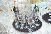 Wedding decor, wine glasses and champagne flutes on table. Decoration with bottles and glasses of champagne on festive table. Luxurious wedding decoration on restaurant table. Elegant event