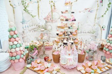 Wedding decoration with pastel colored cupcakes, meringues, muffins and macarons. Elegant and luxurious event arrangement with colorful macaroons. Wedding dessert with macaroons