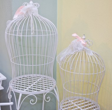Two bird cages with white metal as a symbol of captivity and being trapped or in a confined prison cell. Beautiful decorative cages with pink ribbons. Wedding decoration.