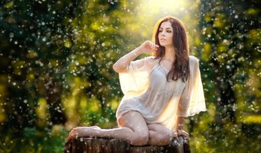 Young beautiful red hair woman wearing a transparent white blouse posing on a stump in a green forest. Fashionable sexy attractive girl sitting on hub in sunny day. Gorgeous redhead in garden.