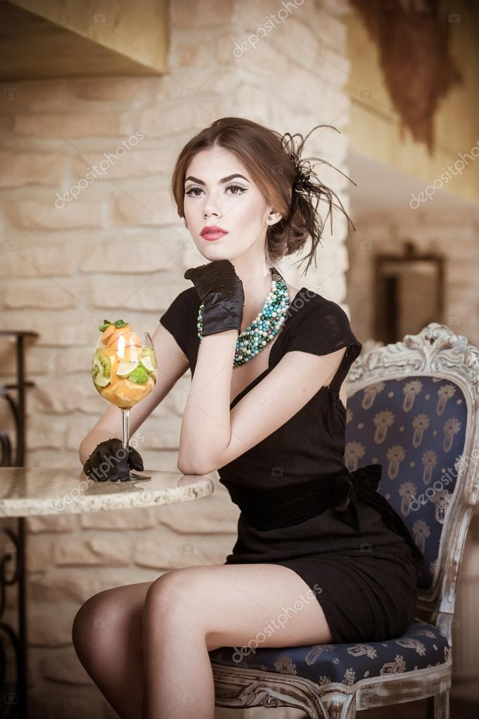 3fec51cfd Fashionable attractive young woman in black dress sitting in ...
