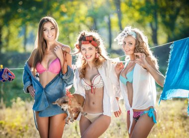 Three sexy women with provocative outfits putting clothes to dry in sun. Sensual young females laughing putting out the washing to dry in sunny day. Perfect body housewives with a dog, shot in forest