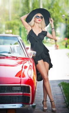 Summer portrait of stylish blonde vintage woman with long legs posing near red retro car. fashionable attractive fair hair female with black hat near a red vehicle. Sunny bright colors, outdoors shot.