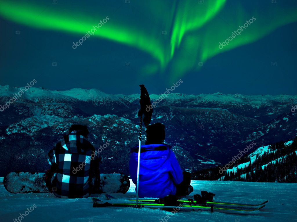 Northern lights over snow mountain peak