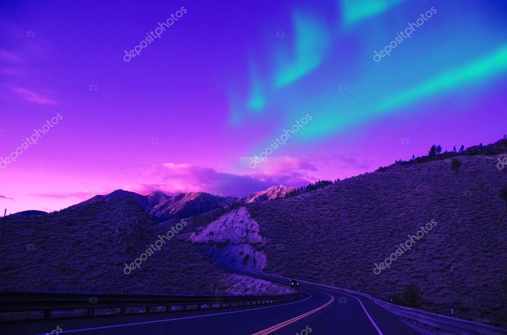 Northern lights over mountain highway