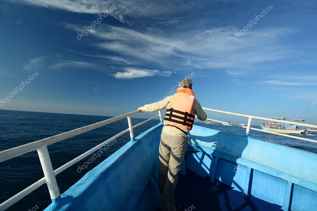 Tourist in boat watching whale