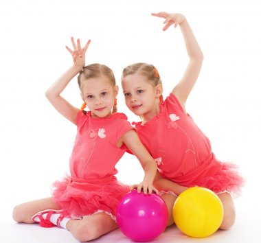 Two charming sisters love to play ball.
