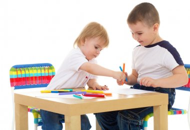 two boys enthusiastically paint markers