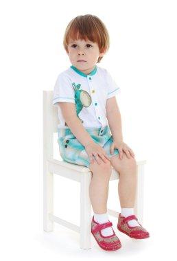 Little boy sitting on a chair.