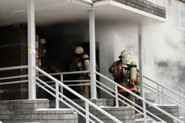 Firefighters team at burning house