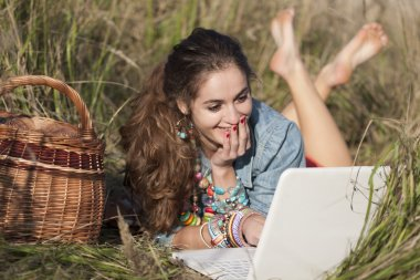 Young woman lying in field and smiling at white laptop