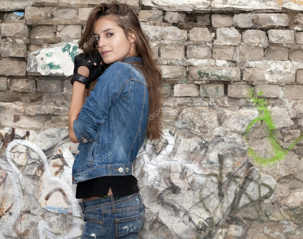 Urban girl in jeans and black gloves standing side view ...