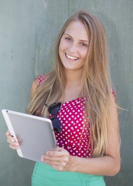 Beautiful smiling girl holding tablet computer