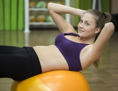 Young woman working out on fitness ball