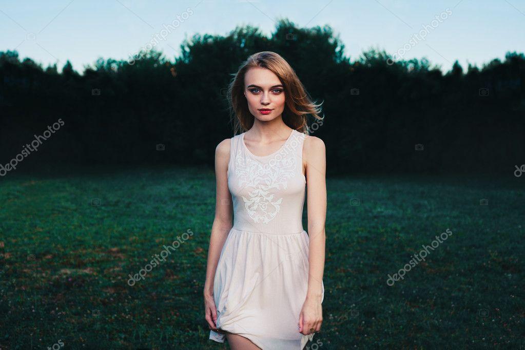 fabulous portrait woman in dress standing in field with flowers