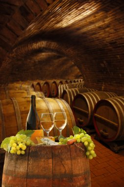 Wine cellar with glasses of white wine against wine barrels