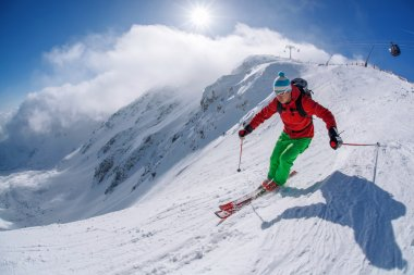 Skier skiing downhill in high mountains during sunny day