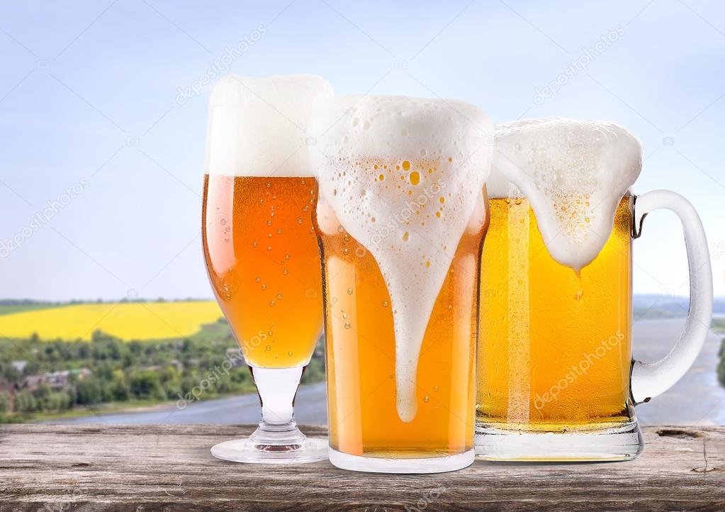 Frosty glass of light beer with summer scene background